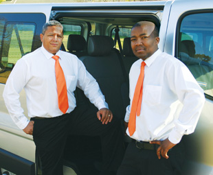 Owner Euan Borah (right) and driver Francis Maselwa (left) stand proud next to one of the vehicles.