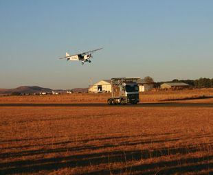 In a daring display of trust, a plane lands on top of an Actros (opposite) as it speeds down the runway.
