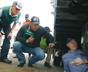 Vic Oliver (left) and Adrian van Tonder watch closely as Dammann (right) checks the fuel level of a vehicle during Truck Test 2014.