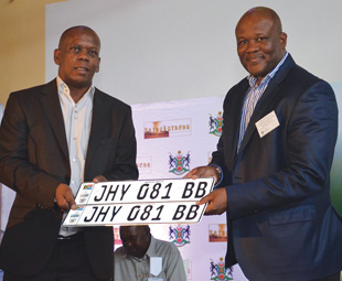 HOD Bailey Mahlakoleng (left) hands over a set of securitised number plates to MEC Gaoage Molapisi of the Bokone Bophirima Department of Community Safety and Transport Management.