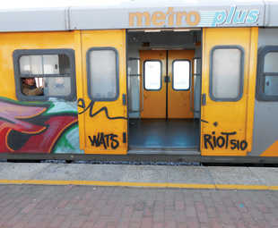 A commuter waits in a graffiti-smeared Metrorail train carriage heading to Bellville, Cape Town.